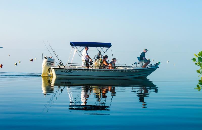 Familie in Fischerboot auf sehr ruhigem Wasser, in dem der Ozean in den Himmel weg von Cudjoe-Schlüssel Florida USA circa im Augu lizenzfreie stockfotografie