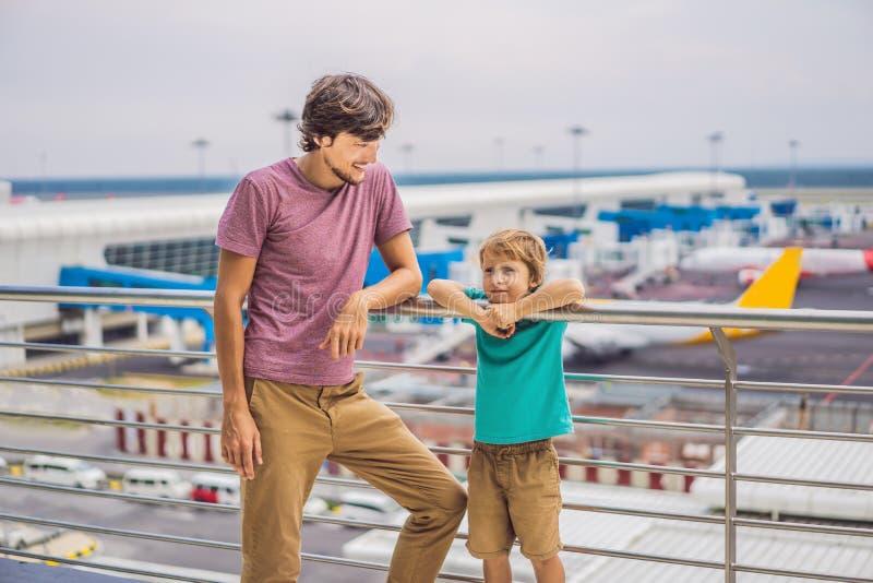 Familie am Flughafen vor Flug Vati und Sohn, die warten, um an Ausgang des modernen internationalen Anschlusses zu verschalen lizenzfreies stockbild