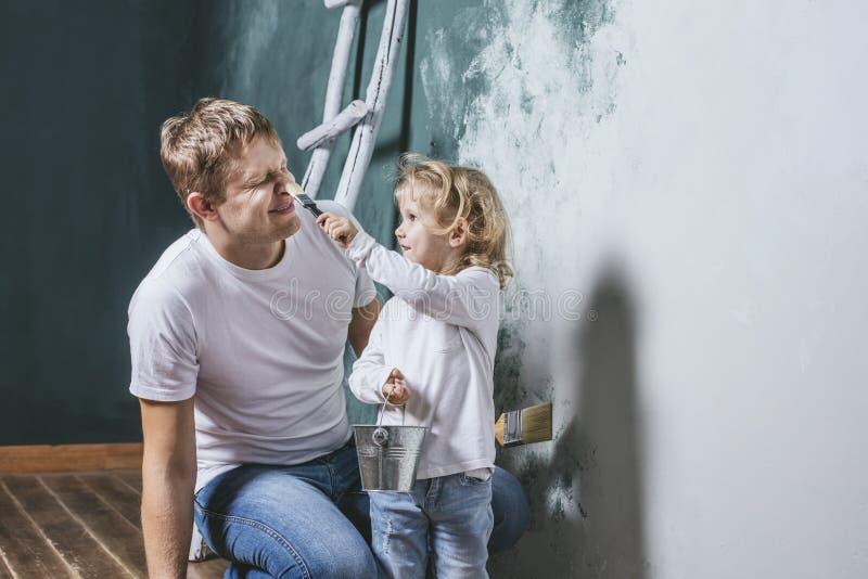 Familie, glückliche Tochter mit dem Vati, der Hauptreparatur tut, Farbenwände, stockbild