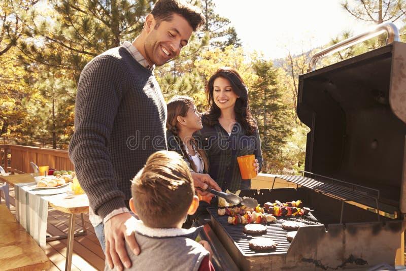 Familie het barbecuing op een dek in het bos stock foto