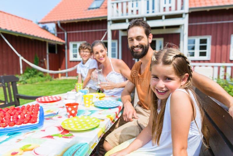 Familie het drinken koffie en het eten van cakevoorzijde van huis stock afbeeldingen