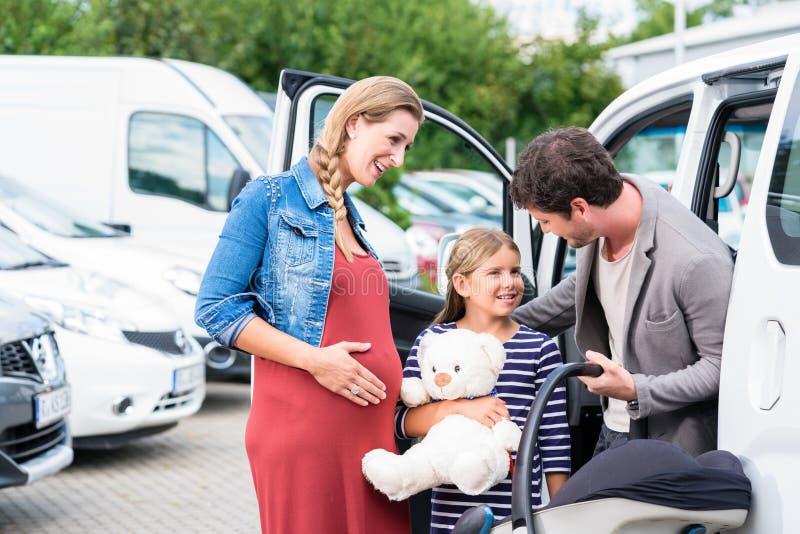 Familie het kopen auto, moeder, vader en kind bij het handel drijven royalty-vrije stock foto's