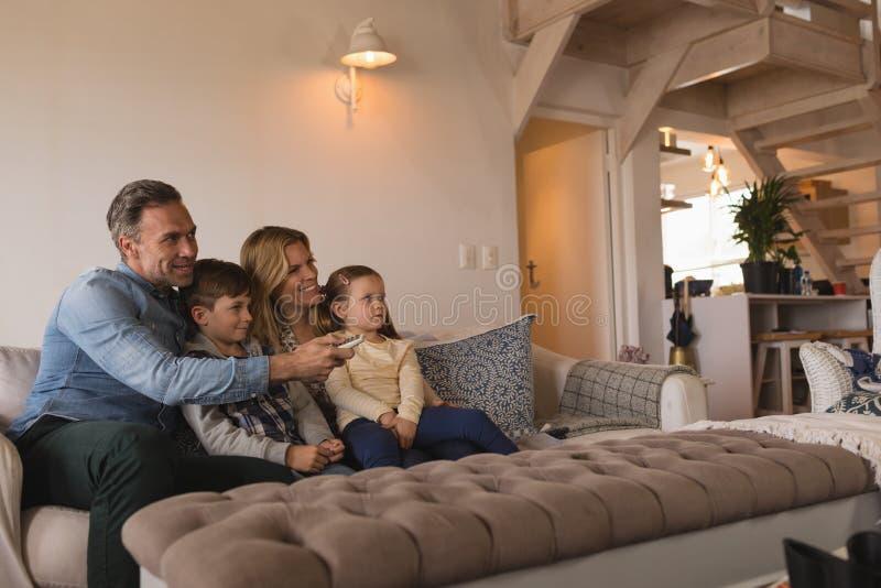 Familie het letten op televisie in woonkamer thuis royalty-vrije stock fotografie