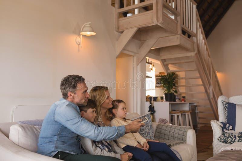 Familie het letten op televisie in woonkamer thuis stock afbeeldingen