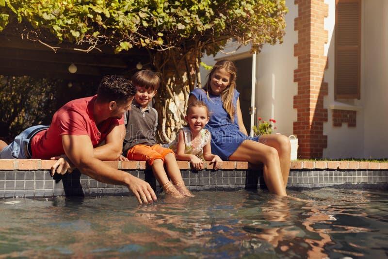 Familie het ontspannen door de pool stock afbeelding