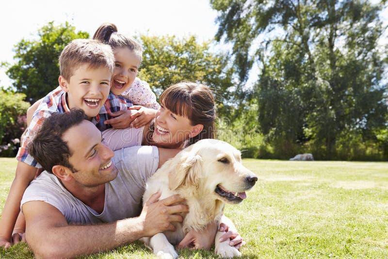 Familie het Ontspannen in Tuin met Huisdierenhond royalty-vrije stock foto's