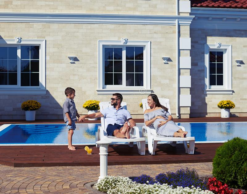 Familie het ontspannen voor modern huis met pool royalty-vrije stock foto