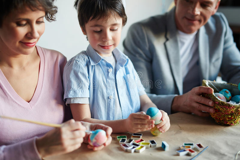 Familie het schilderen eieren stock foto's