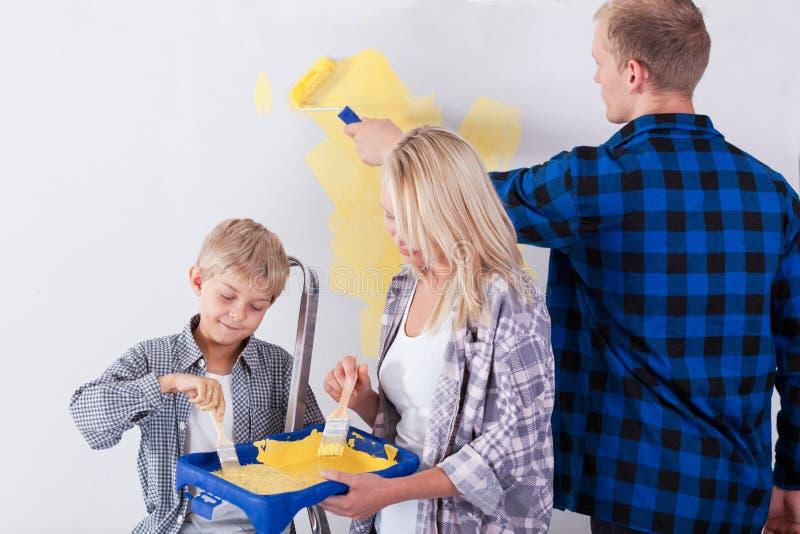 Familie het schilderen muur stock foto