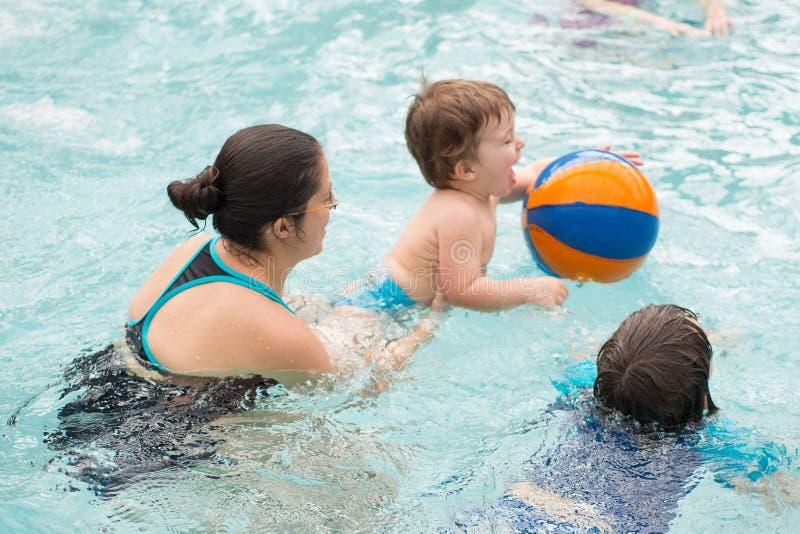 Familie het spelen in de pool stock foto