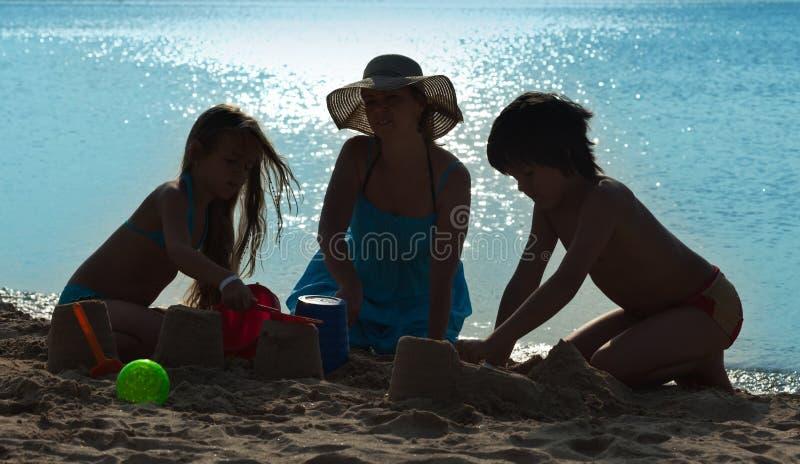 Familie het spelen op het strand - silhouetten royalty-vrije stock afbeeldingen