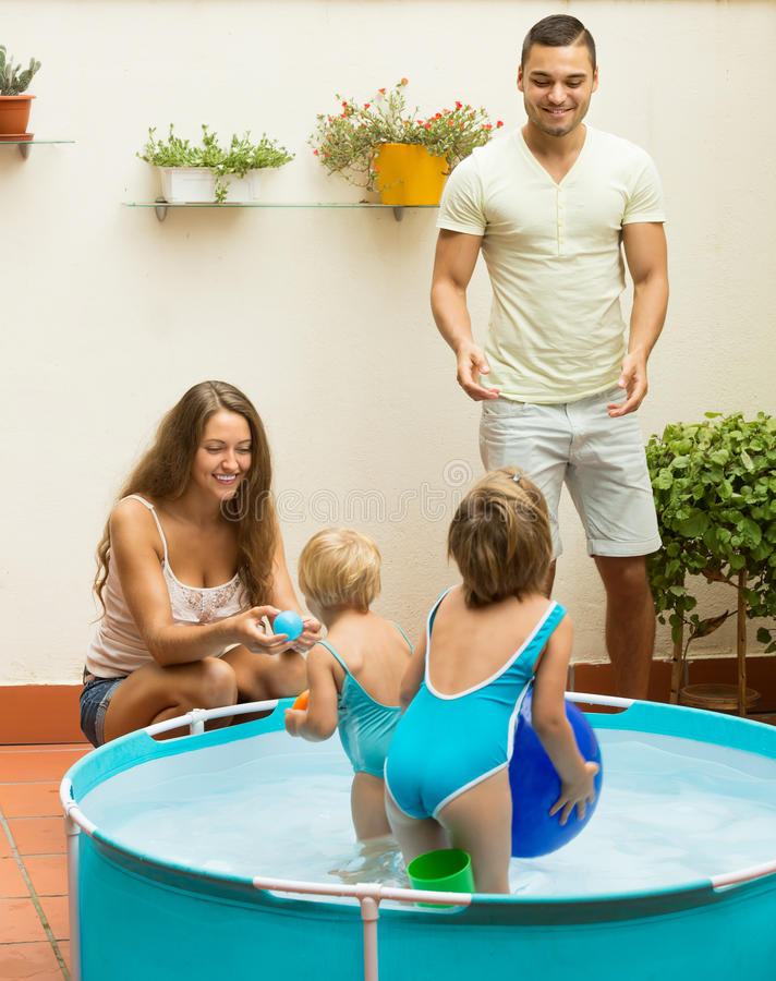 Familie het spelen in pool bij terras stock afbeelding