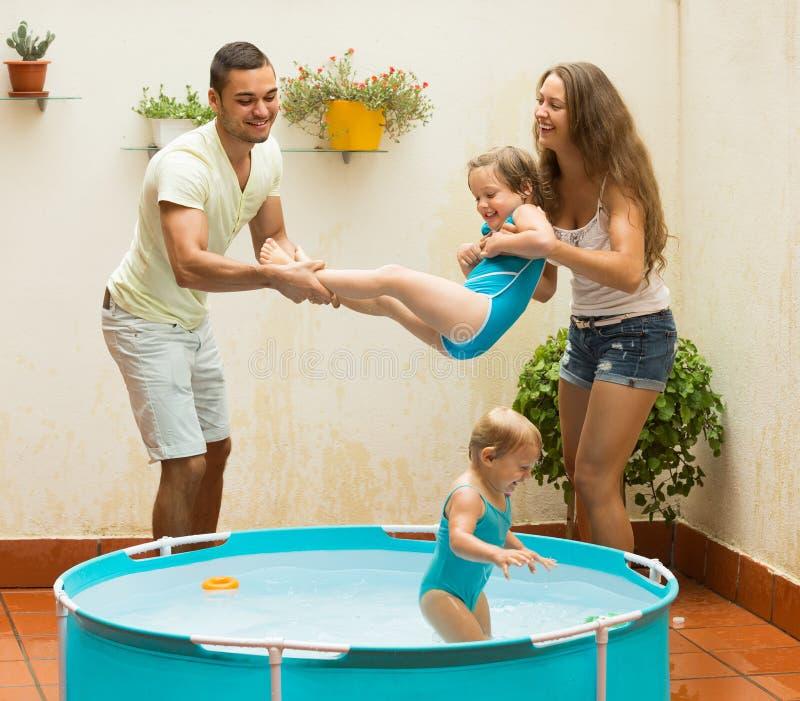 Familie het spelen in pool bij terras stock foto's
