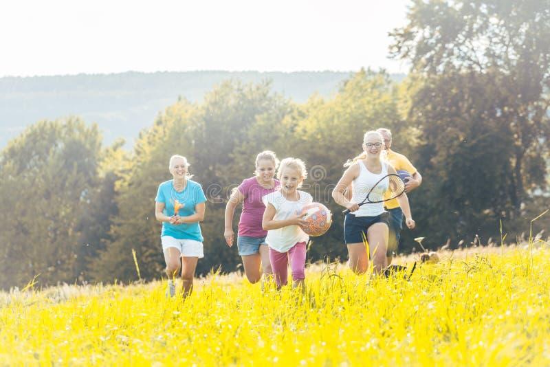 Familie het spelen van, het runnen van en het doen van sport in de zomer royalty-vrije stock foto