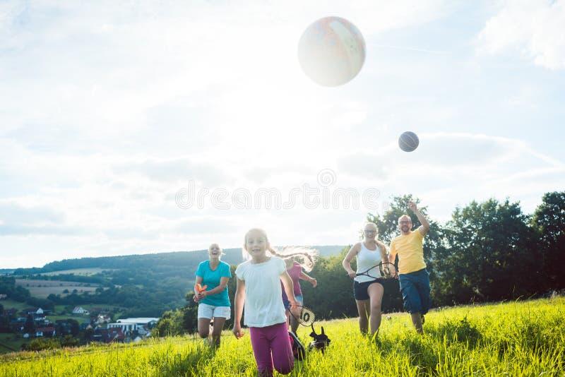 Familie het spelen van, het runnen van en het doen van sport in de zomer royalty-vrije stock fotografie
