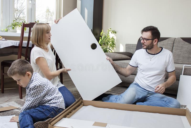 Familie het verdraaien van meubilair Het mamma en de papa vouwen meubilair De kindjongen leest zorgvuldig de assemblageinstructie stock afbeelding