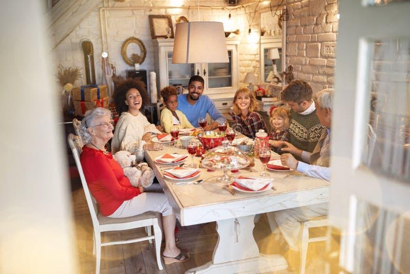 Familie het vieren de Kerstmistijd en geniet Kerstmis van traditioneel diner stock fotografie
