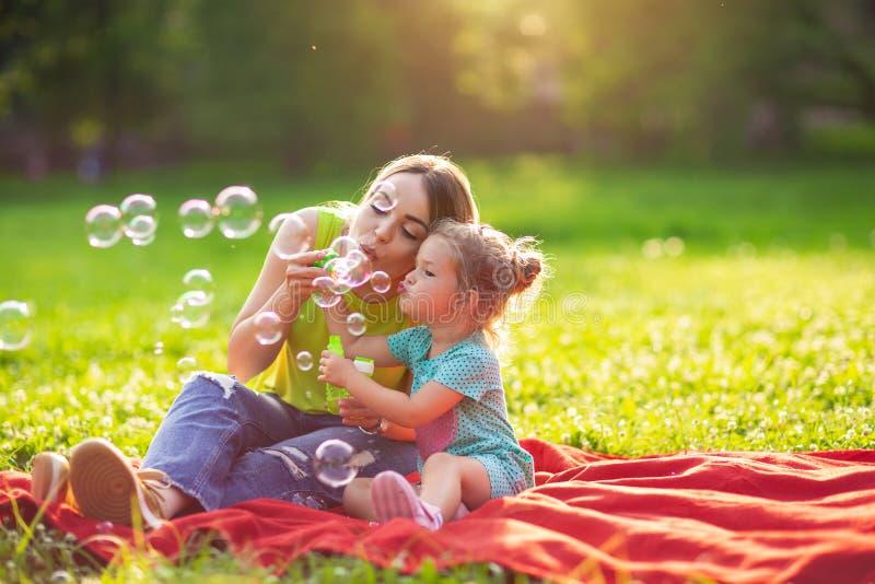 Familie im Park - weibliches Kind brennt Suppenschaum durch und macht Blasen wi lizenzfreie stockbilder