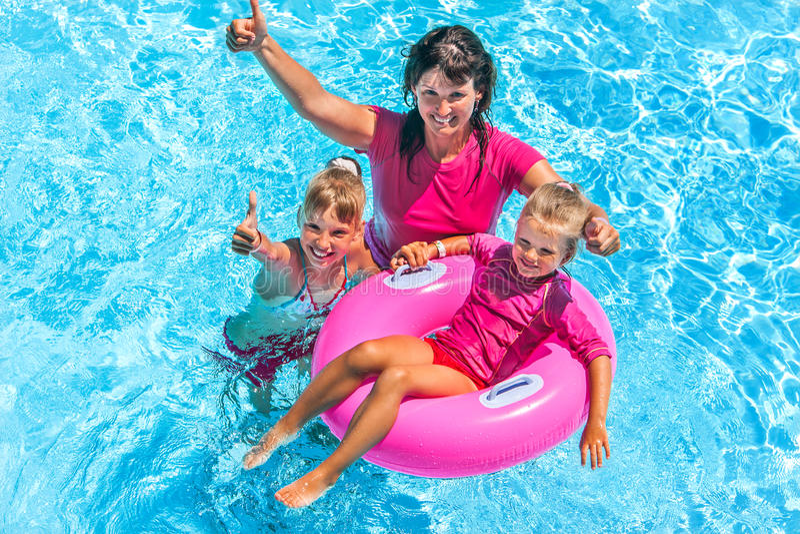 Familie im Swimmingpool stockbilder