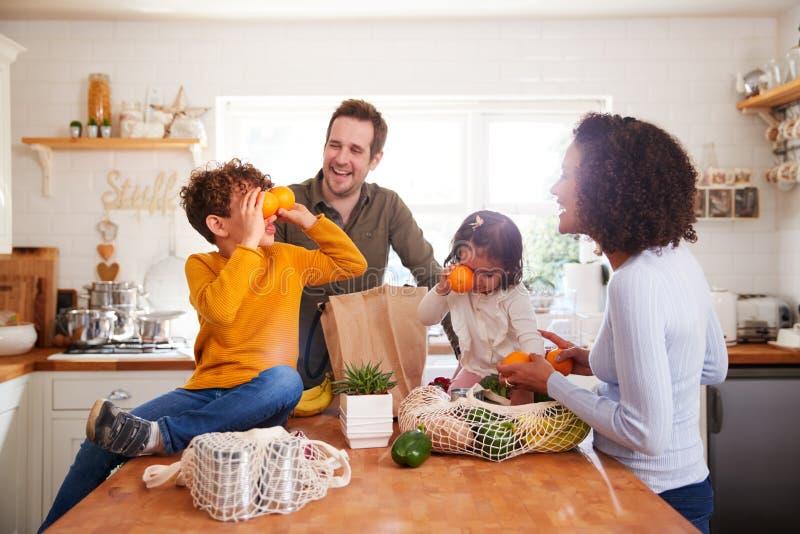 Familie keert terug uit de winkelwagentjes met plastic gratis zakken die boodschappen uitpakken in keuken