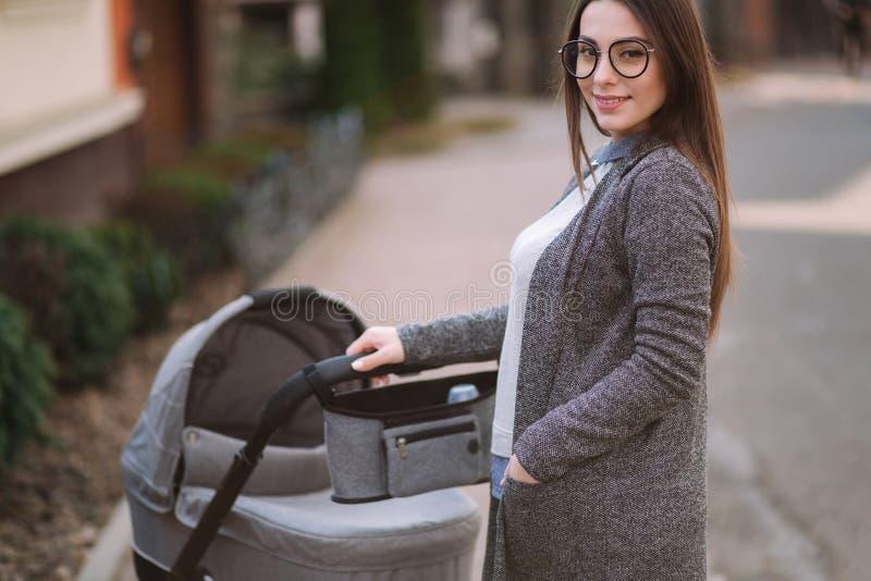 Familie, kind en ouderschapconcept - Gelukkige moeder met wandelwagen in het park Mamma met zonnebril en modieuze grijs stock foto