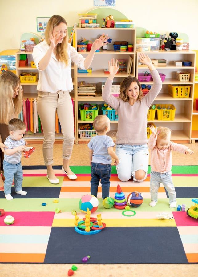 Familie, kinderjaren, activiteiten en creativiteitconcept - gelukkige ouders en hun kleine jonge geitjes die een pret in speelkam stock afbeelding