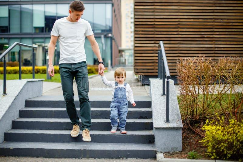 Familie, kinderjaren, vaderschap, vrije tijd en mensenconcept - de gelukkige jonge vader en weinig dochter wandelen door de strat stock foto's
