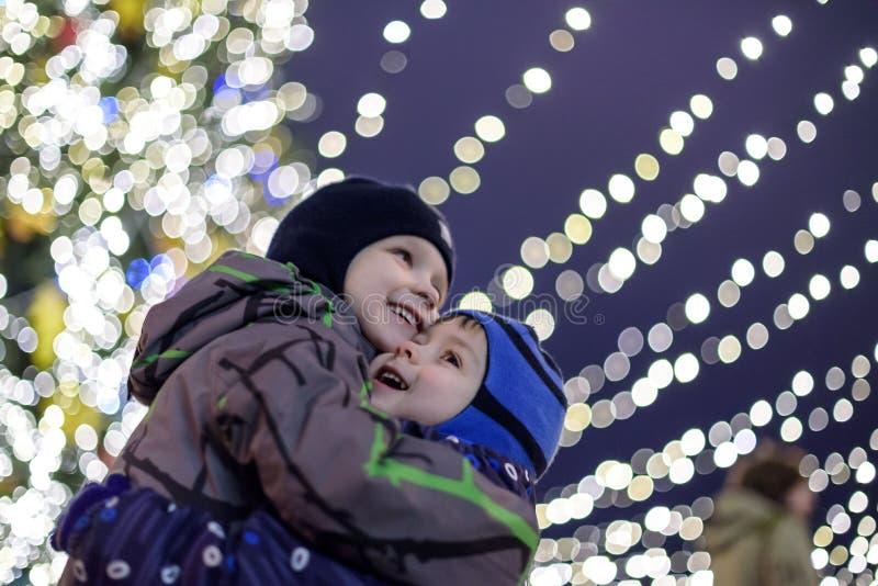 Familie, Kindheit, Jahreszeit und Leutekonzept -, das im Winter glücklich ist, kleidet über schneebedecktem Stadthintergrund stockfotos