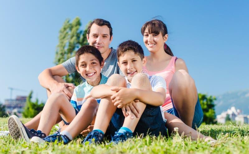 Familie kleidete im Weiß im Park im Sommer an, der in der Wiese sitzt stockfotos