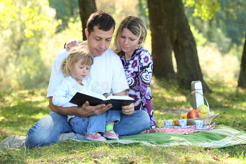 Familie las die Bibel in der Natur stockfotografie