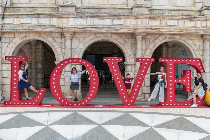 Familie in Macao, LIEFDEbrieven die in openlucht grote het van letters voorzien rode pret en reis stellen royalty-vrije stock afbeeldingen