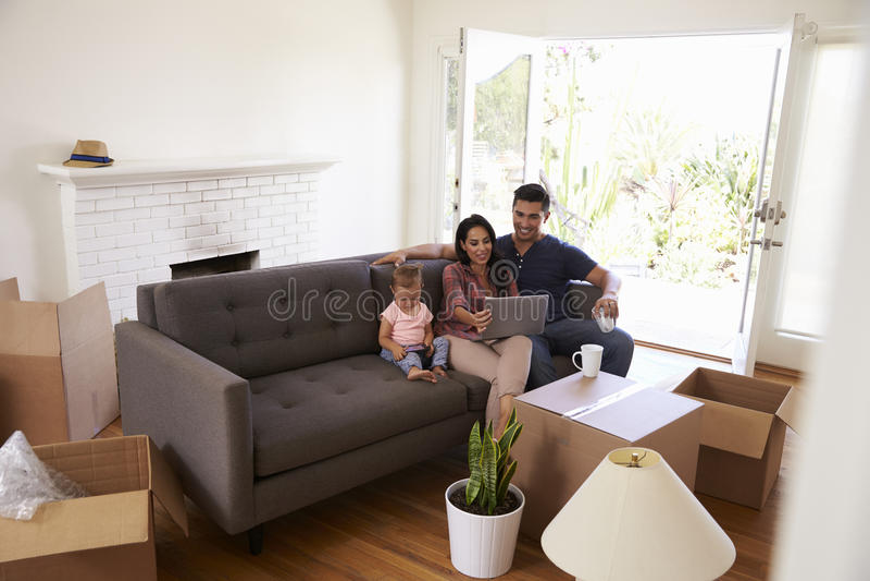 Familie machen eine Pause an Sofa Using Laptop On Moving-Tag lizenzfreie stockfotografie