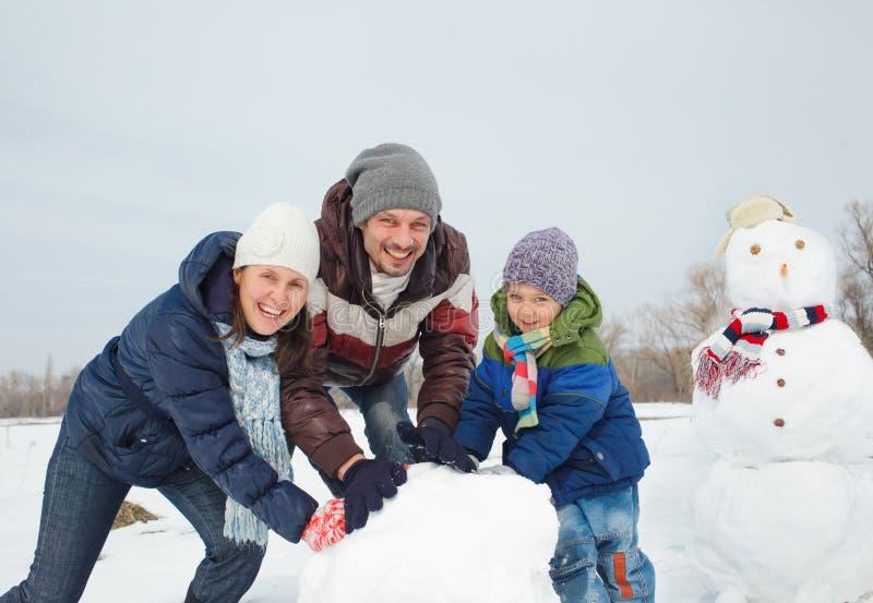 Familie machen einen Schneemann stockfotografie