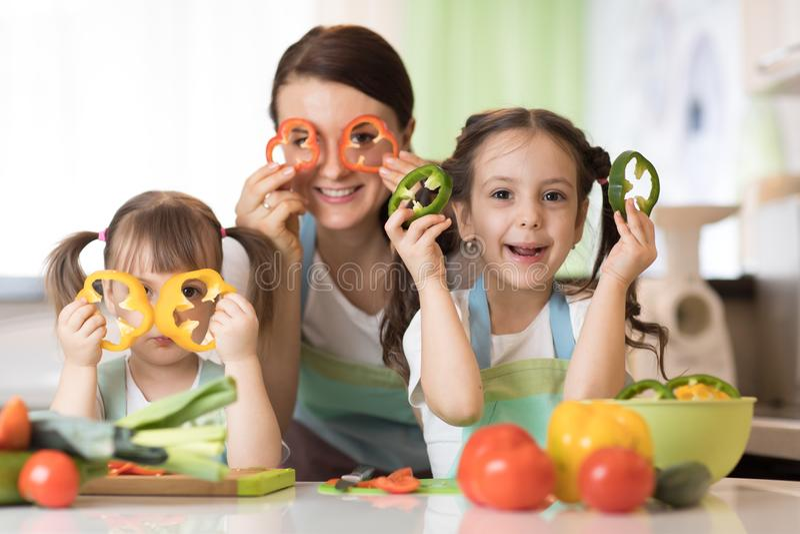 Familie - mamma en haar kinderen die pret in de keuken hebben royalty-vrije stock afbeelding