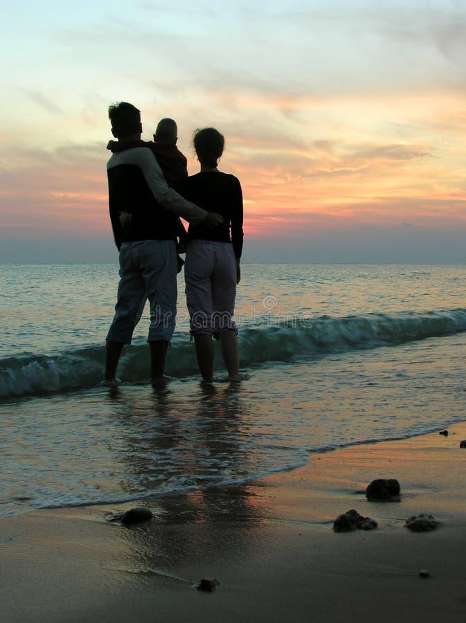 Familie. Meer. Sonnenaufgang. stockbild