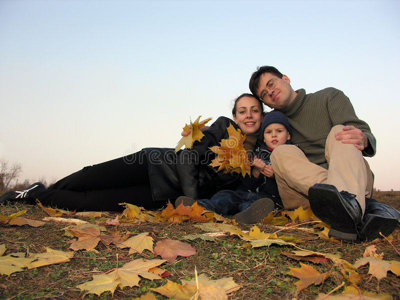 Familie met de herfstbladeren royalty-vrije stock afbeeldingen
