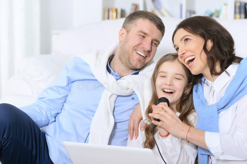 Familie met dochter het zingen karaoke stock afbeeldingen
