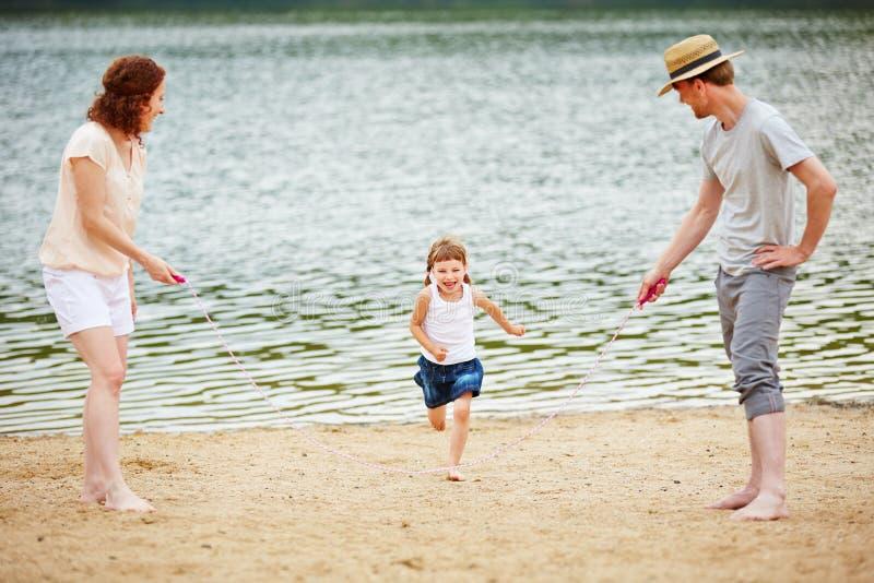 Familie met dochtertouwtjespringen in de zomer stock afbeeldingen
