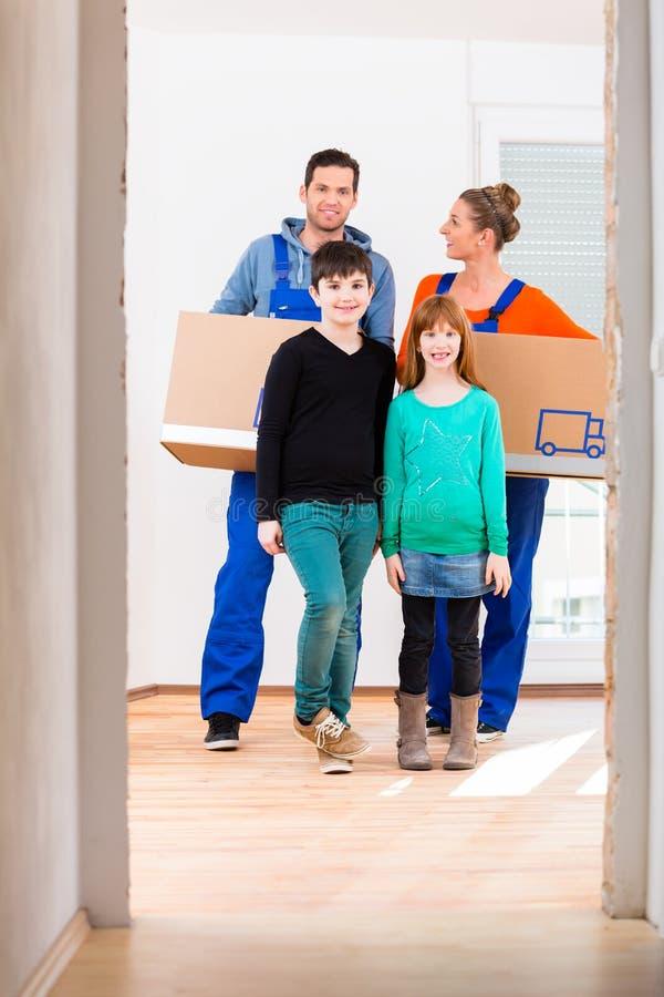 Familie met dozen die zich in nieuw huis bewegen royalty-vrije stock foto
