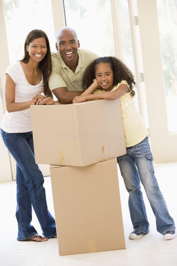 Familie met dozen in het nieuwe huis glimlachen royalty-vrije stock afbeeldingen