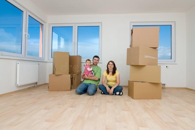 Familie met dozen in nieuw huis royalty-vrije stock afbeelding