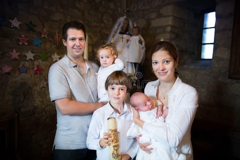 Familie met drie kinderen die het doopsel vieren stock afbeelding