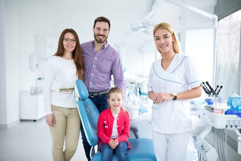 Familie met een glimlachende jonge tandarts stock fotografie