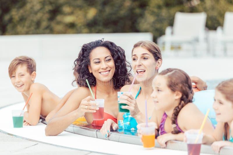 Familie met glazen sap in zwembad stock afbeeldingen
