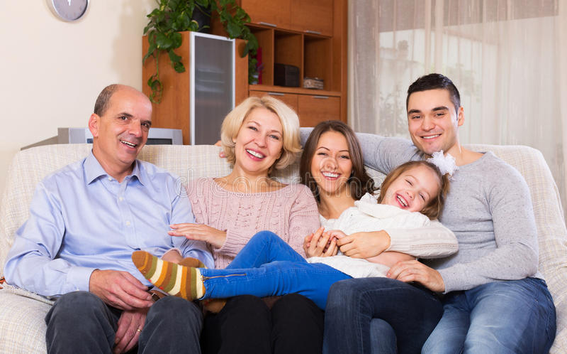 Familie met grote kinderen die binnen stellen stock foto's