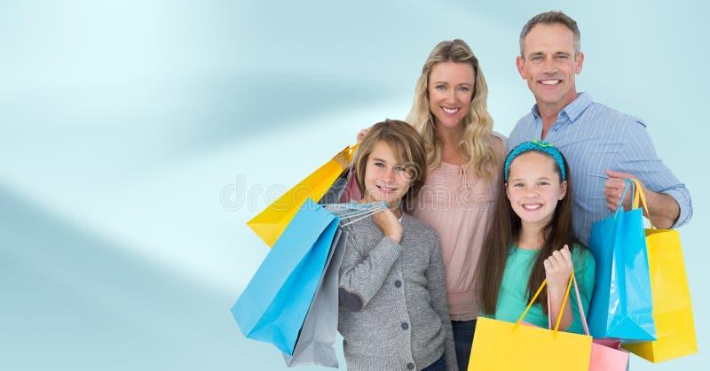 Familie met het winkelen zakken tegen onscherpe blauwe abstracte achtergrond stock foto