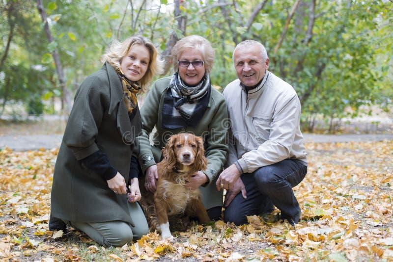 FAMILIE MET HOND IN DE HERFSTpark stock afbeelding