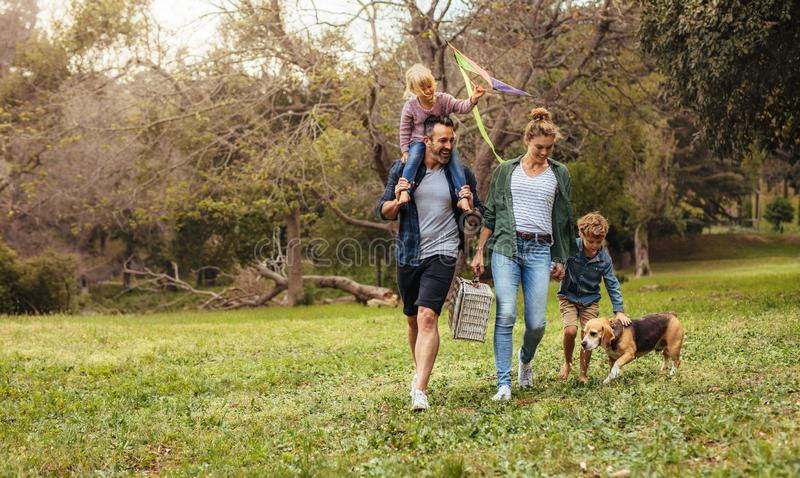Familie met hond die op picknick in park gaan stock afbeeldingen