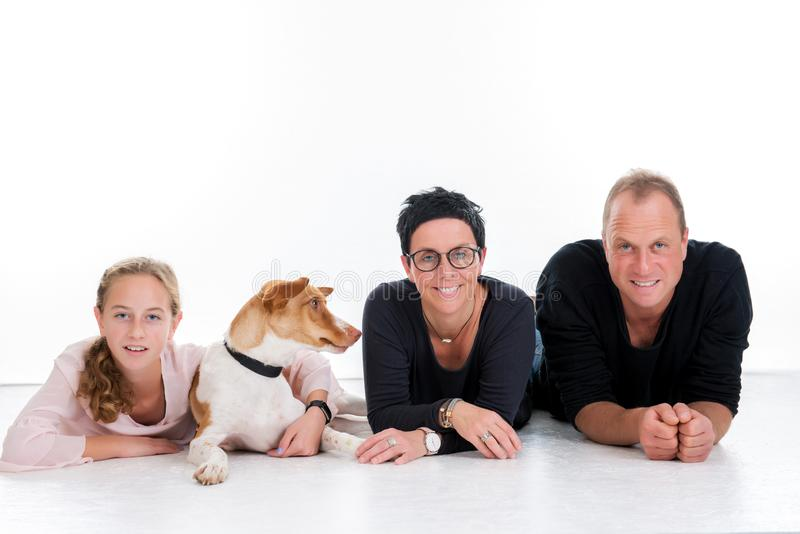 Familie met hond die voor witte achtergrond liggen stock foto