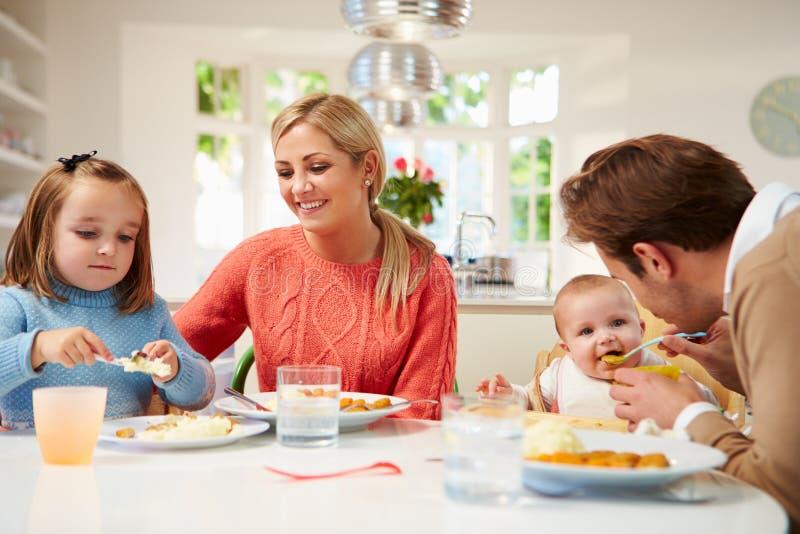 Familie met Jonge Baby die Maaltijd thuis eet royalty-vrije stock afbeelding